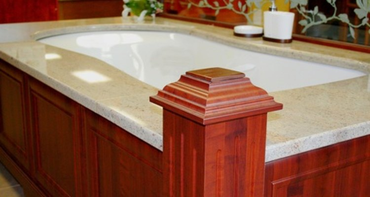 This mahogany-trimmed tub is toned down by its grey stone border.