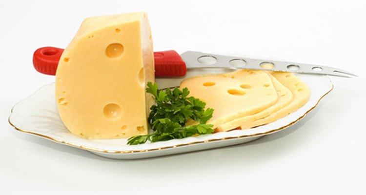 El queso suizo tiene una apariencia lisa y es de color amarillo pálido.