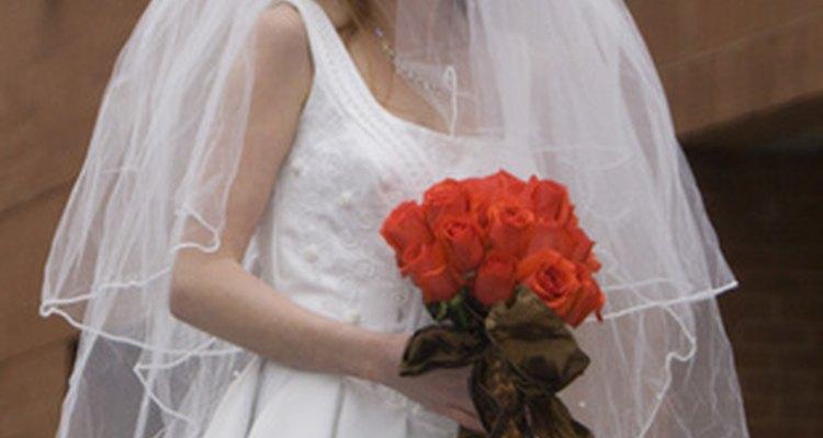 Novia tradicional con vestido blanco y velo, con un ramo de rosas rojas.