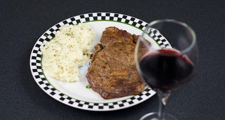 Un bistec con un vaso de vino.