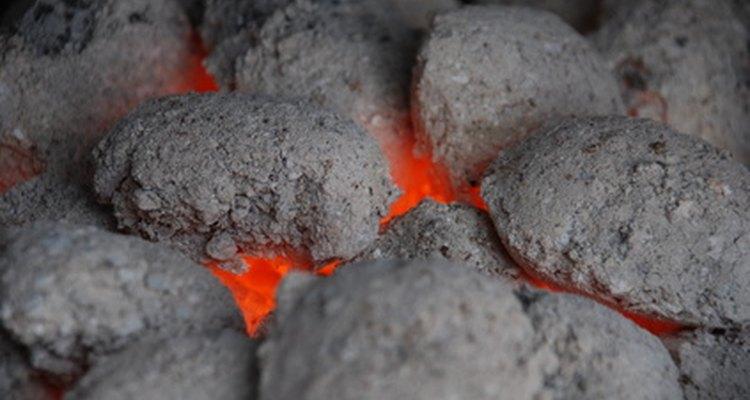 Distribuye los carbones calientes de igual forma a cada lado del recipiente.