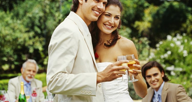 newlywed couple holding glasses of wine at their wedding reception
