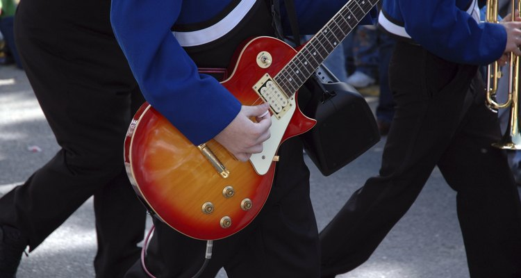 Estudiante en uniforme con una guitarra para la práctica de la banda.