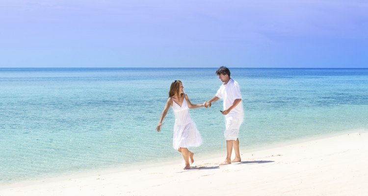 Beautiful young couple running on a tropical beach