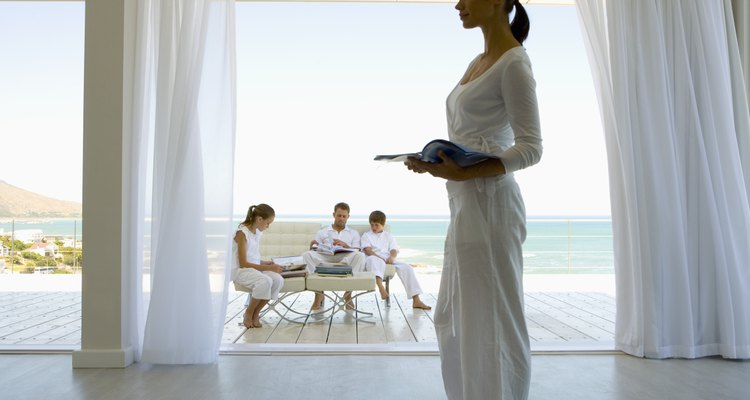 Woman standing with book and family sitting on deck by beach