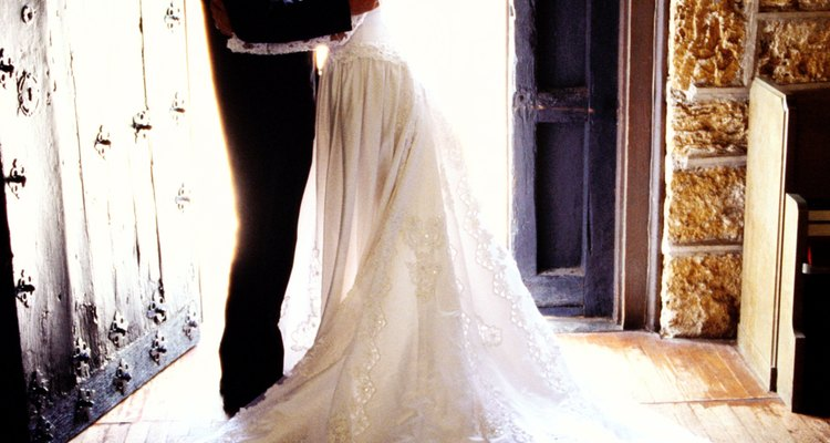 side view of a bride and groom holding each other at the entrance to the church