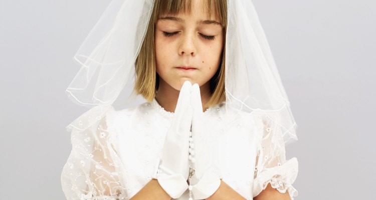 girl (11-13) standing praying wearing her first holy communion dress