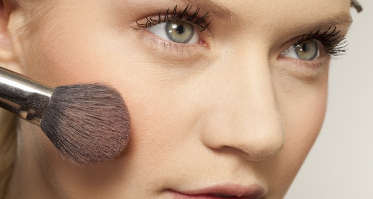Young woman applying make up with brush, close up