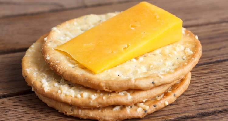 Three golden cheese crackers on wood. With cheese.
