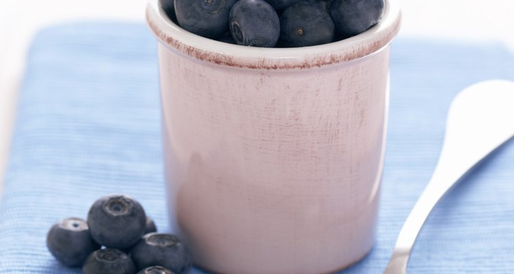 Spoon and blueberries in jar on blue cloth