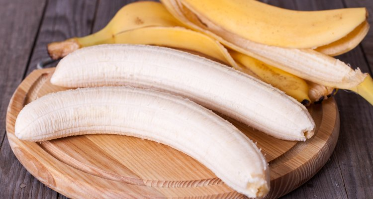 Peeled banana on a wooden board