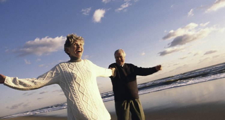 Senior couple holding hands on beach