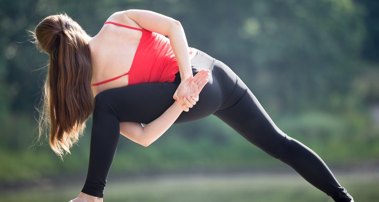 Fit young beautiful woman wearing red tank top and black sporty leggings working out outdoors in park on summer day, doing parivritta parshvakonasana variation with hands behind back, rear view