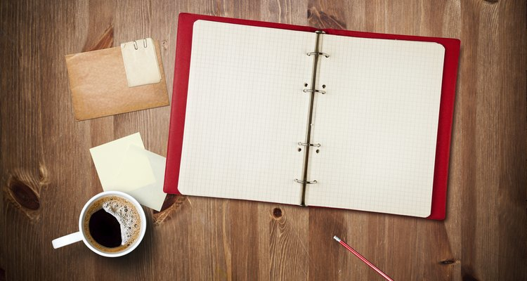 Workspace with coffee cup, note paper and notebook