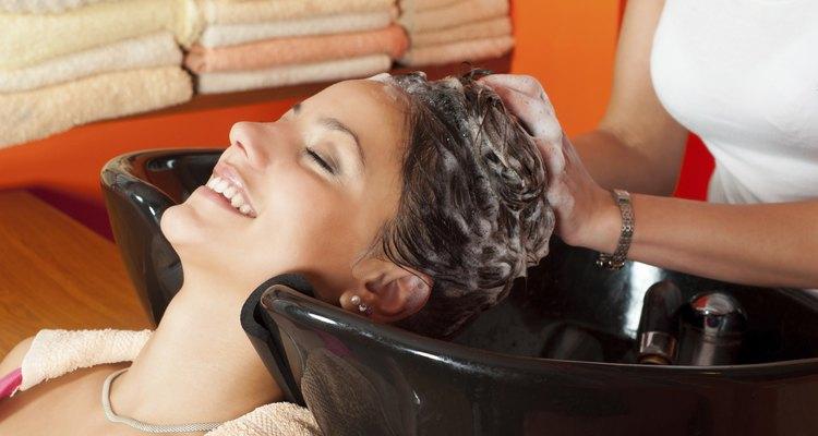 Beautiful girl washing hair in hairdressing salon