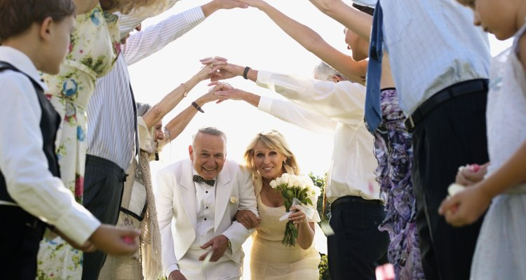 Bride and groom walking under arms of wedding guests