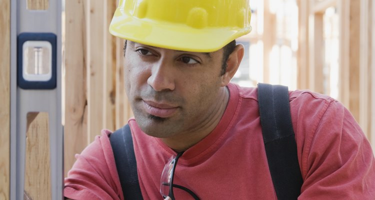Mixed Race male construction worker using level