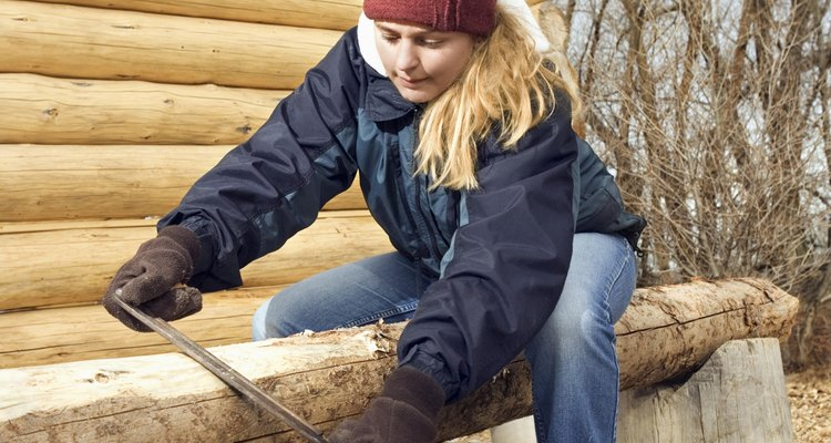 A draw knife is used to strip bark from logs.