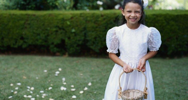 Flower girl (4-7) holding basket of petals, portrait, smiling