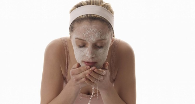 Woman washing face with facial mask