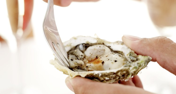 person eating an oyster from an oyster shell