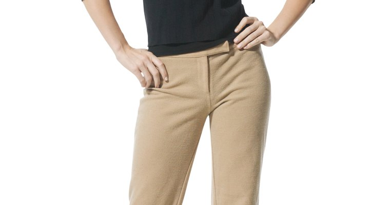an attractive caucasian woman in tan pants and a black shirt smiles brightly