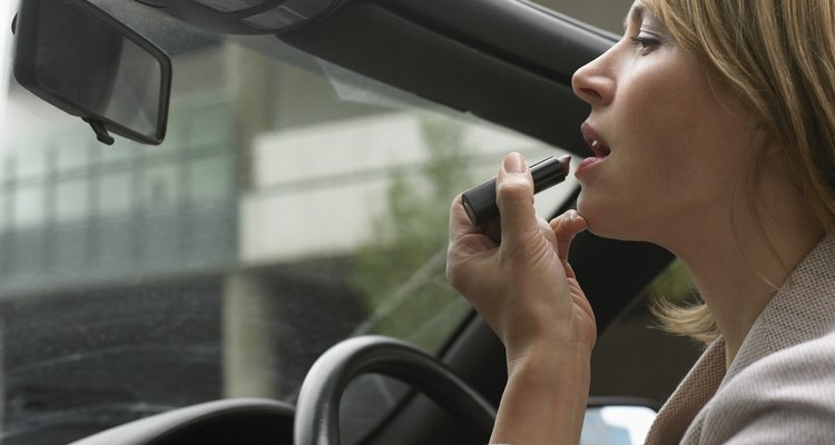 Woman Sitting Applying Make-up in a Vehicle Mirror