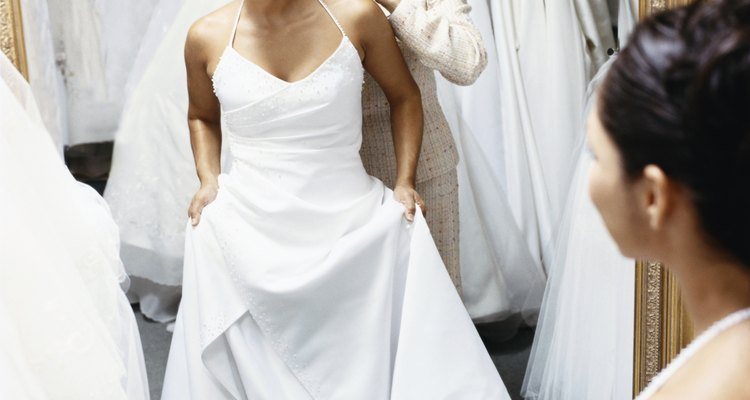 Senior Woman Helping Her Daughter Try on a Wedding Dress in Front of a Mirror in a Bridal Shop