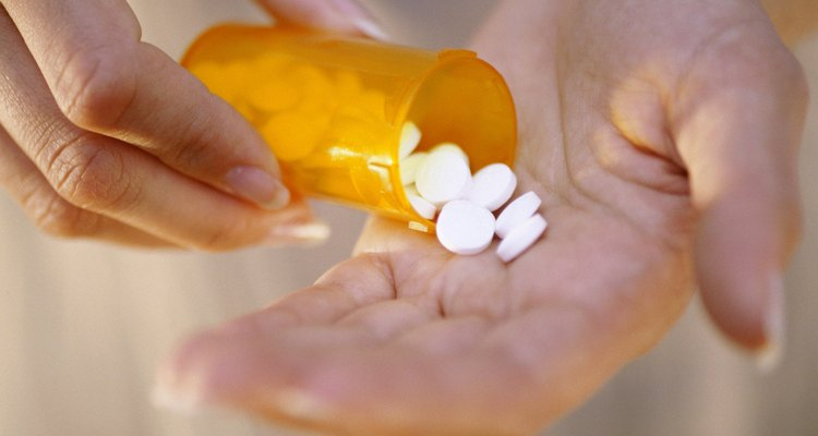 Close-up of a person's hand holding a bottle of pills