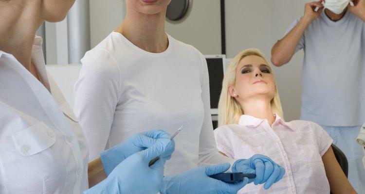 Los asistentes dentales se preparan para ayudar al dentista en el examen de un paciente.