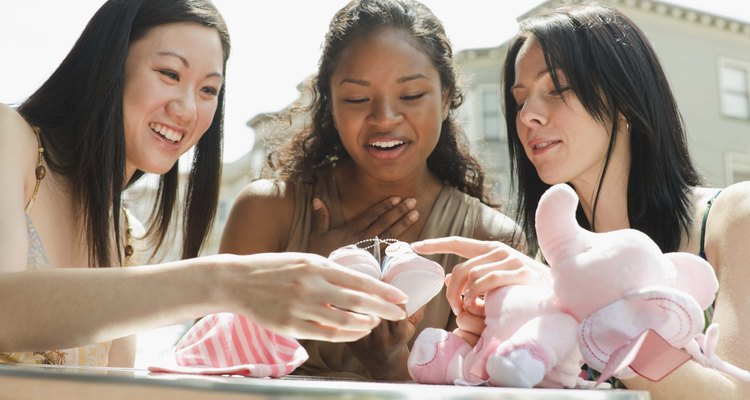Women opening baby shower gifts