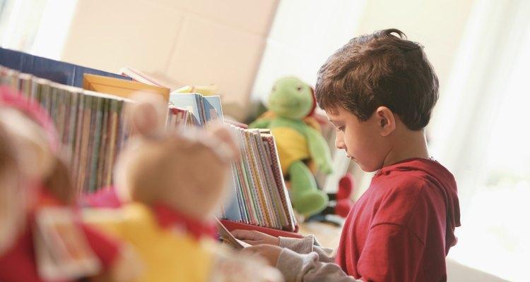 Un pequeño niño mirando un libro en la biblioteca.