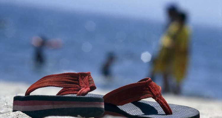 Photo, a close-up of thong sandals sitting on a beach, Color