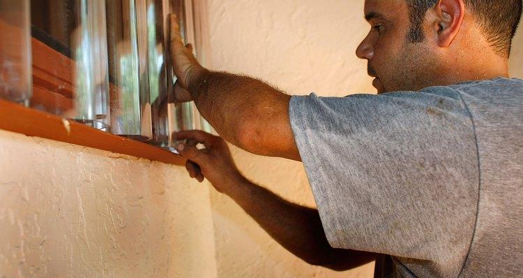 Instalando painéis de plexiglas para a preparação para um furacão