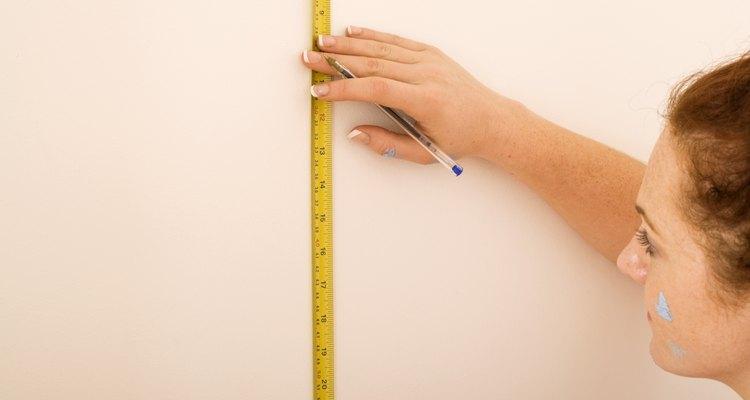 Woman measuring wall