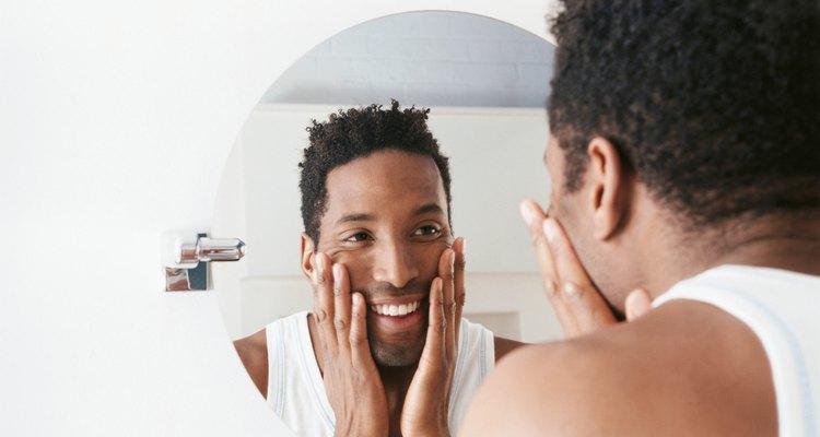 Man looking in wall mirror