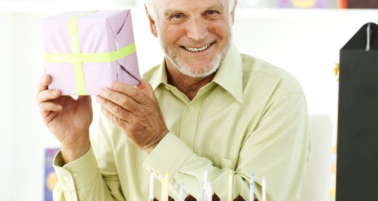 portrait of an elderly man holding up a present for a birthday celebration