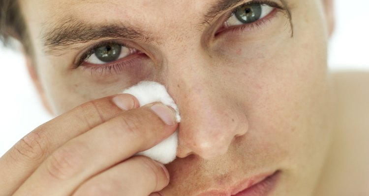 portrait of a young man cleaning his face with cotton wool