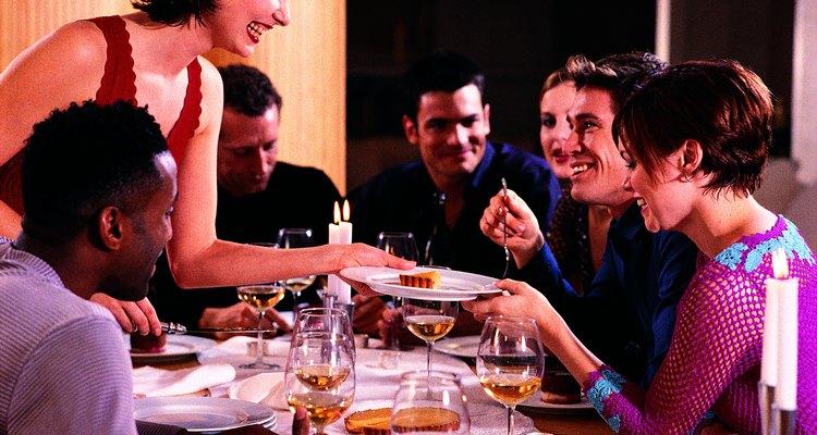 Friends chatting while hostess serves dessert