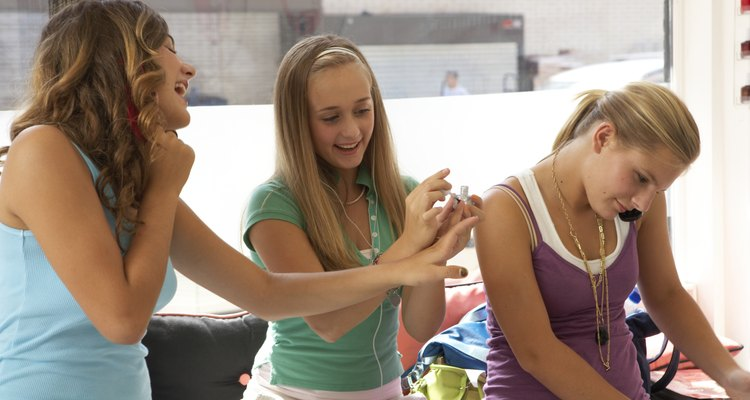 Young woman using mobile phone, friend painting friend nails, smiling