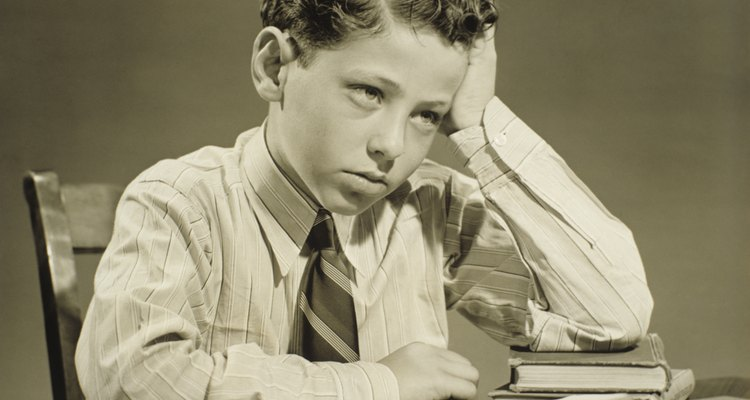 Boy (10-11) sitting at table over open book, head resting on hand, (B&W), close-up