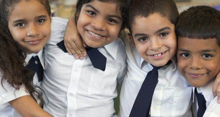 Niños en uniforme abrazándose en el salón de clases.