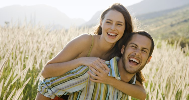 Man giving woman piggyback ride in field