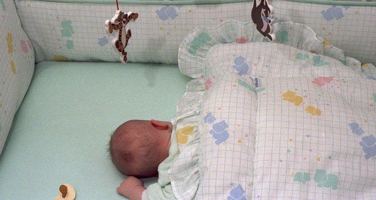 Ángulo superior de un bebé durmiendo en una cuna.
