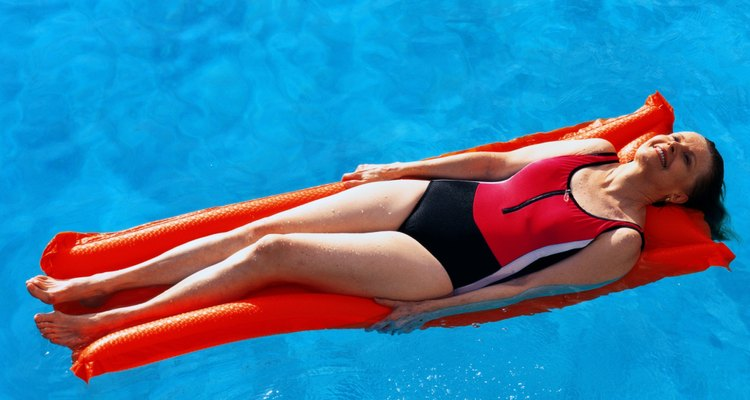 woman floating on raft in swimming pool