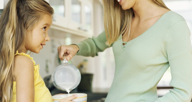 Side profile of a mid adult woman pouring milk into a bowl for her daughter