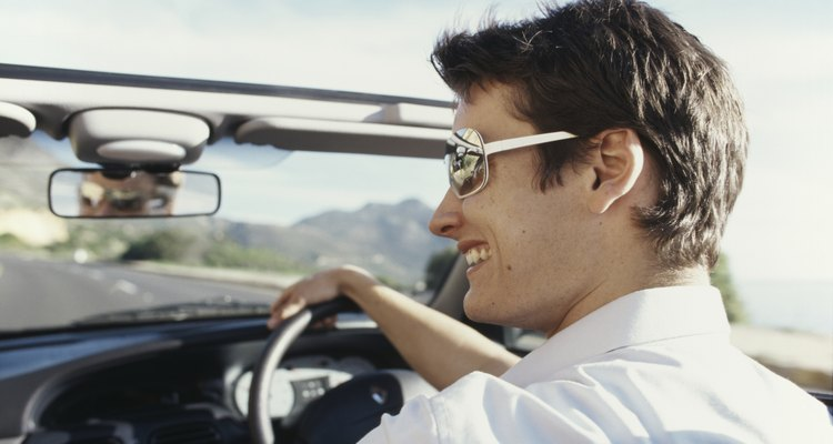 Young man driving in cabriolet car, smiling, rear view