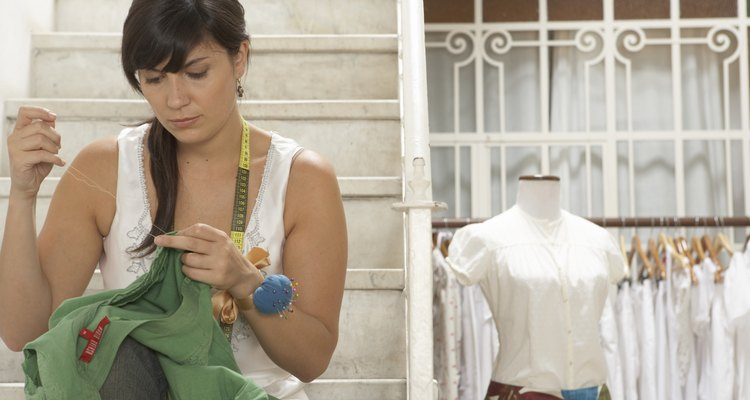 Woman sitting on steps, sewing, with mannequin in background