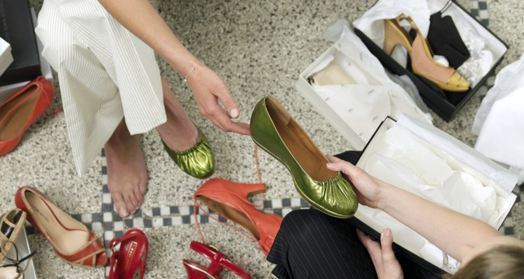Young woman taking shoe from assistant in shop, overhead view