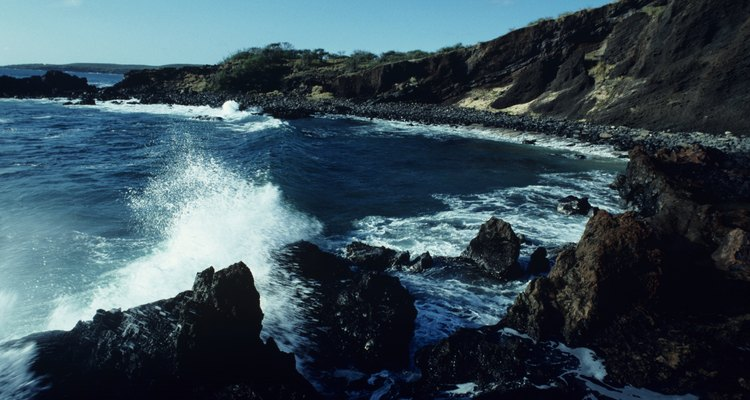 Wave crashing on rocky shoreline, Hawaii, USA